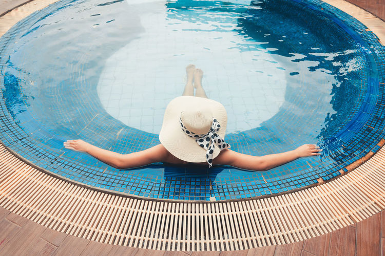 Rear View Of Mid Adult Woman Wearing Hat Swimming In Pool