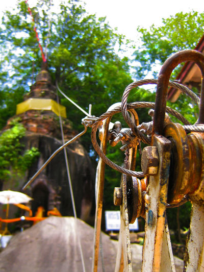 Wire-n-Wat Buddha Buddhist Umbrella Focus On Foreground Pulley Pulley Block Rusty Thai Shrimp Paste Wire Cable