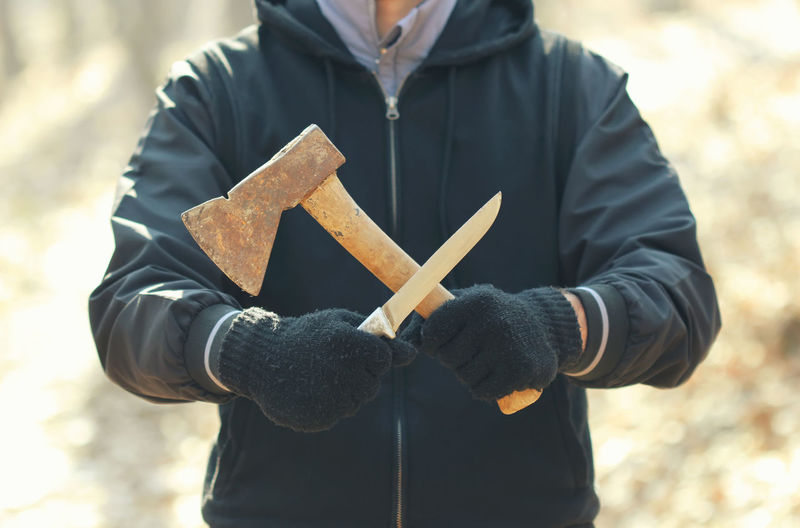 Maniac with knife and axe Adult Angry Crime Knife Aggressive Anger Axe Concept Crazy Danger Dangerous Furious Holding Killer Mad Male Maniac Massacre Murderer Outdoors Outside Psychopath Serial Unrecognizable Person Violence
