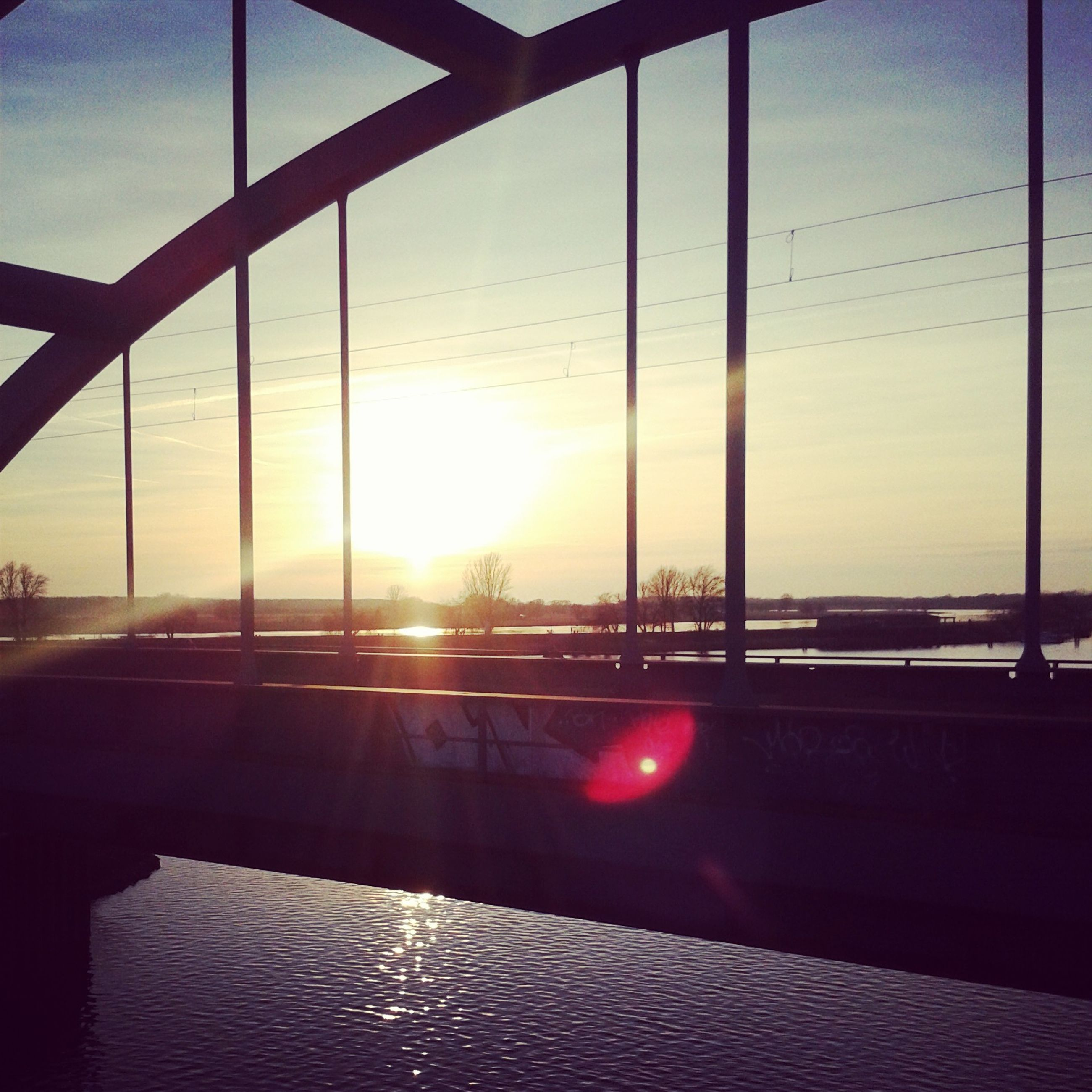 sun, sunset, sunbeam, sunlight, lens flare, glass - material, sky, silhouette, window, indoors, transparent, built structure, transportation, reflection, orange color, architecture, railing, no people, nature, bright