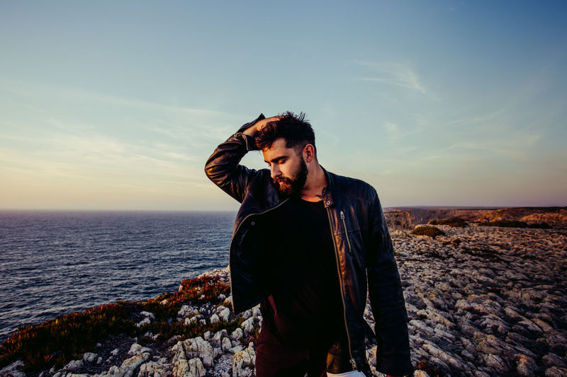 Sky One Person Sea Standing Real People Water Lifestyles Young Adult Front View Nature Scenics - Nature Young Men Horizon Beauty In Nature Land Rock Casual Clothing Solid Horizon Over Water Outdoors Men Fashion Beard Style Sunset