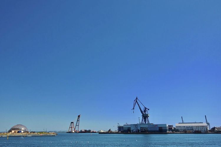 Commercial dock by sea against clear blue sky