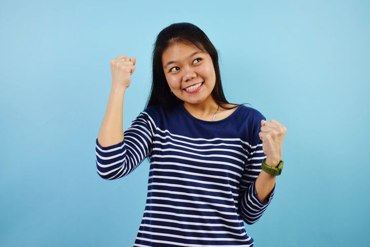 Portrait of a smiling young woman against blue background