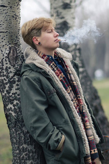Side View Of Young Woman Smoking While Standing By Tree At Park