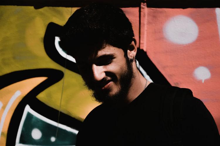 Close-up of smiling man against graffiti wall