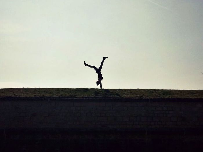 Silhouette man jumping on pole against sky