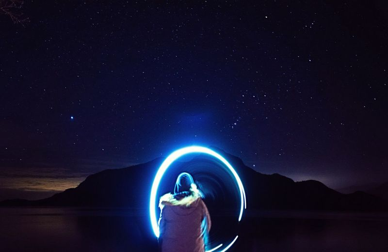 Rear view of person making light painting against sky at night