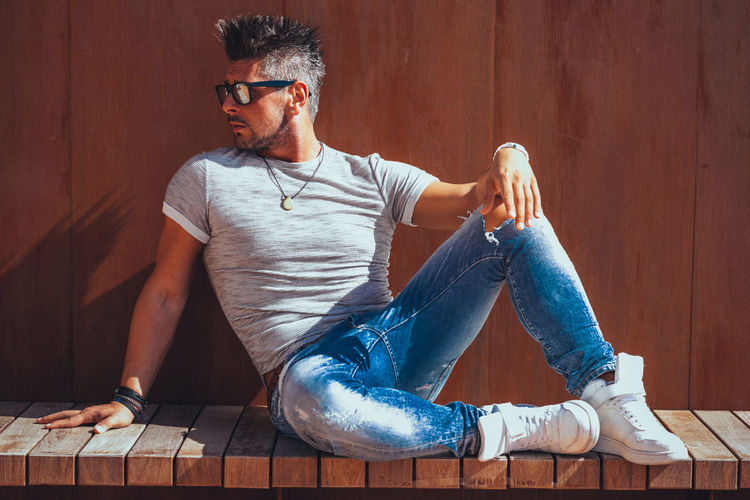 Casual Clothing Full Length One Person Sitting Glasses Young Men Young Adult Real People Beard Front View Lifestyles Eyeglasses  Leisure Activity Facial Hair Men Looking Relaxation Fashion Flooring Jeans Contemplation
