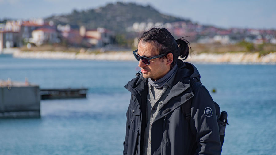 Man wearing sunglasses standing by sea