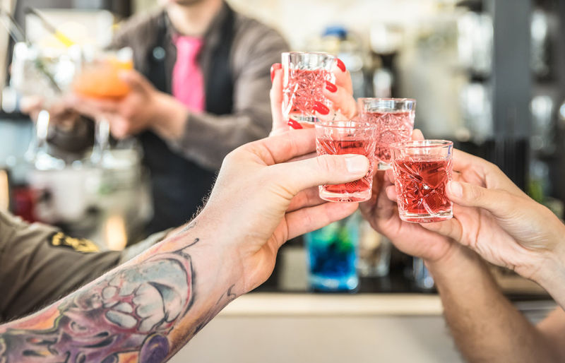 Cropped hands of friends toasting drinks in bar