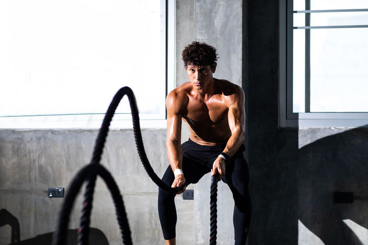 Man exercising with ropes in gym