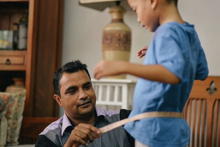 Tailor measuring waist of boy at home