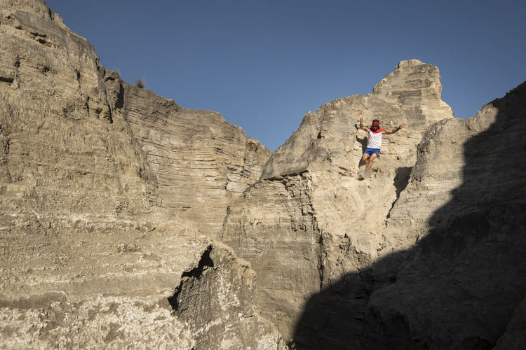 Low angle view of people on rock formation against sky