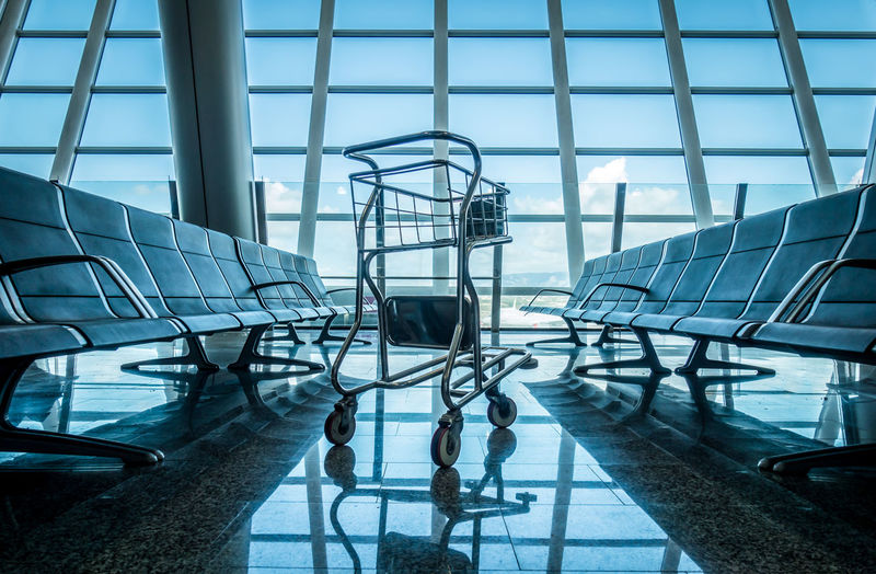 Architecture Reflection Traveling Modern Sky Blue Chair Travel Airport Trolley Day Empty Airport Waiting Benches Seats Indoors  Modern Architecture Seat No People Airport Terminal Built Structure Seating Bench Seating Area Airport Departure Area 17.62°