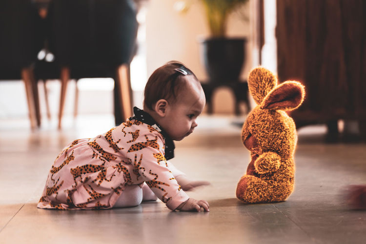 Cute baby girl with toy on floor at home