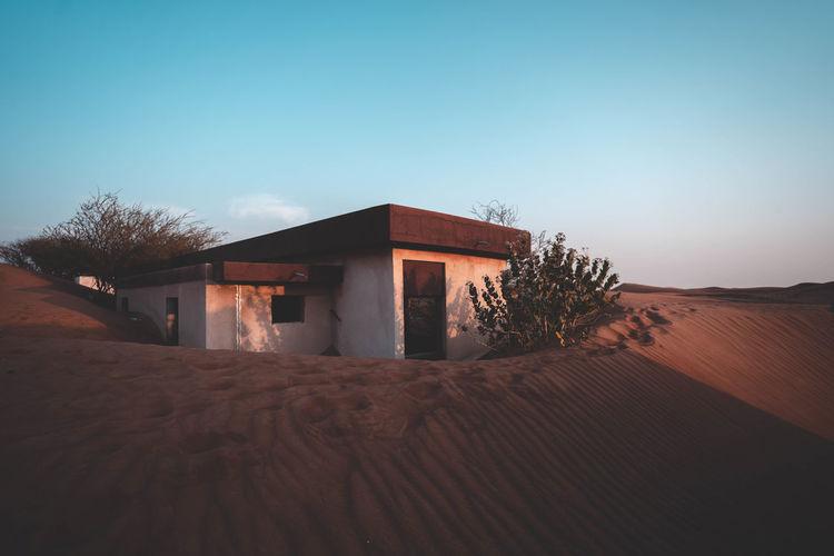 House on sand against clear sky
