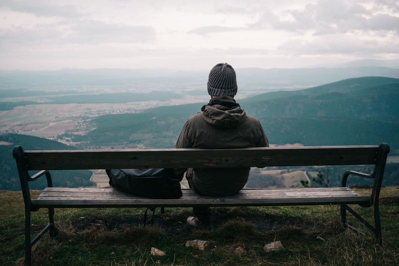 Rear View Of Man Sitting On Bench Against Landscape