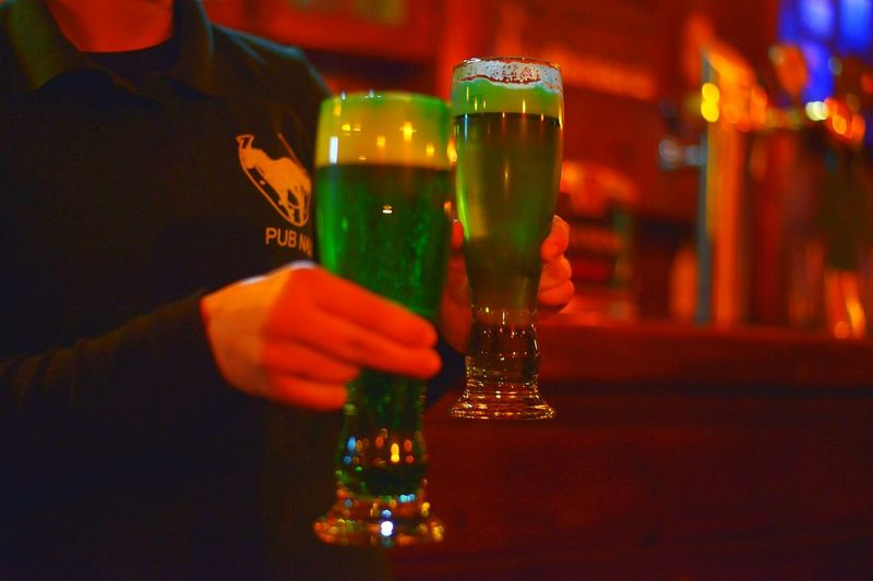 Midsection of bar tender holding green beer glasses in pub