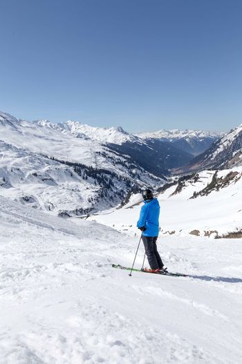 Person Skiing On Snowcapped Mountain Against Clear Sky