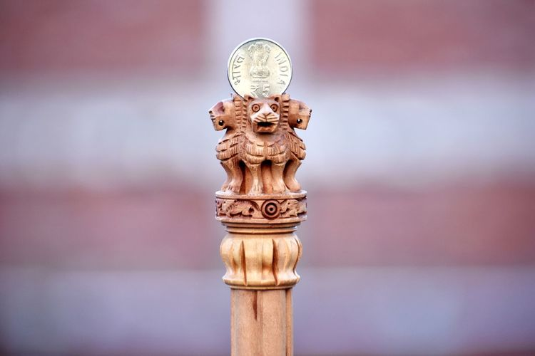 Close-up of coin on wooden lion statues