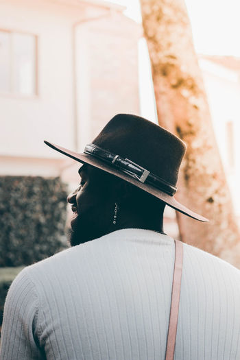 Rear view of man holding hat