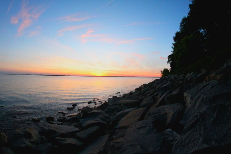 Scenic View Of Rocky Coastline And Sea At Sunset