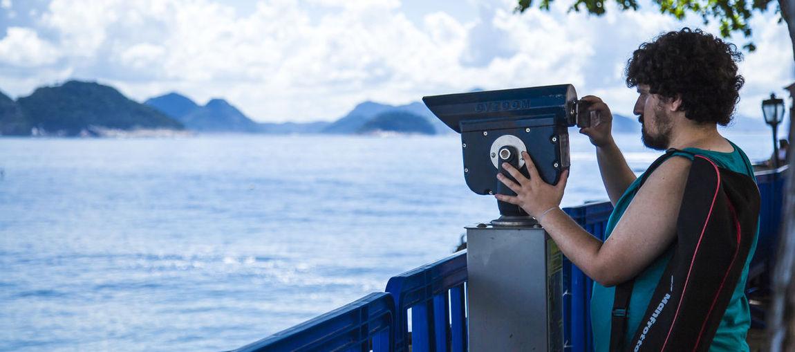 Man looking through binocular by lake