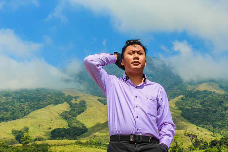 Young man standing on landscape against sky