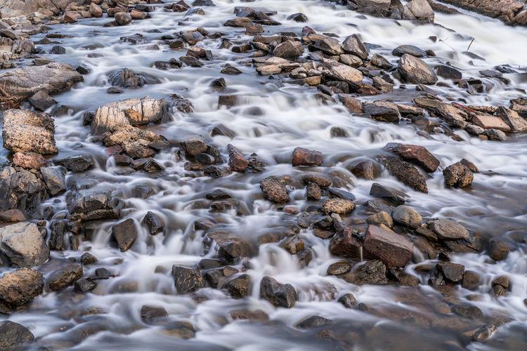 Stream flowing through rocks in winter