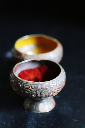 High angle view of turmeric and vermilion in silver containers