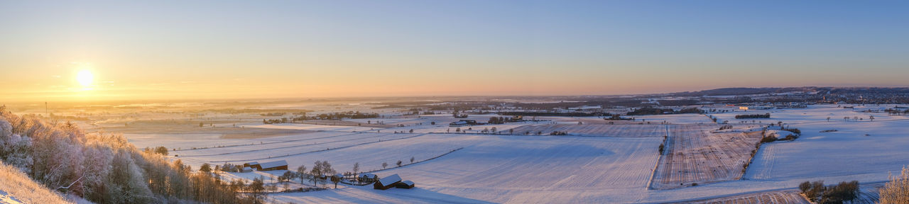 High angle view of snow covered landscape against sky during sunset
