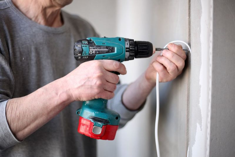 Close-up of man working against wall at home