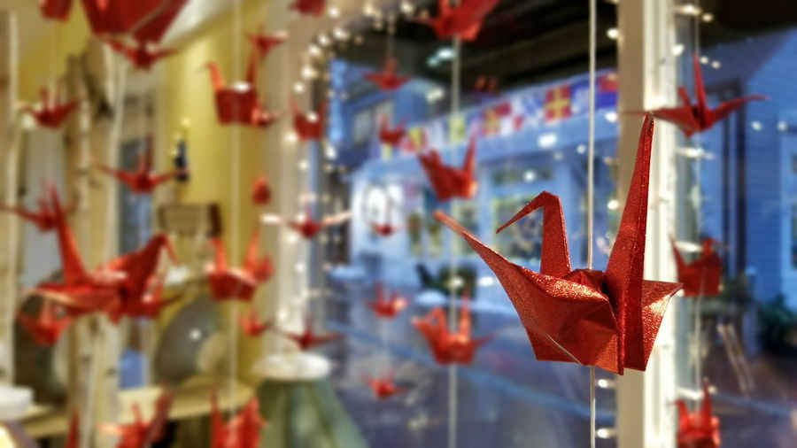 Origami paper cranes hanging against glass window