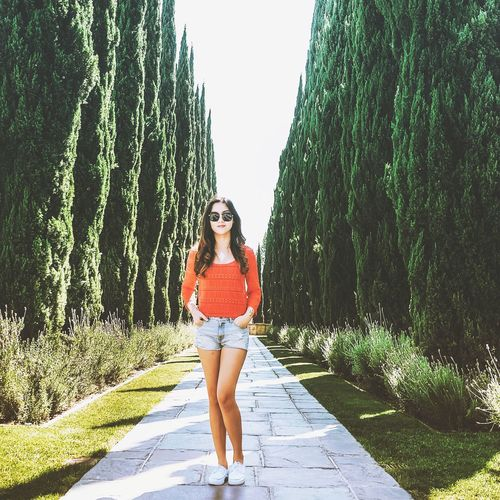 Portrait of beautiful woman standing on garden path surrounding by trees