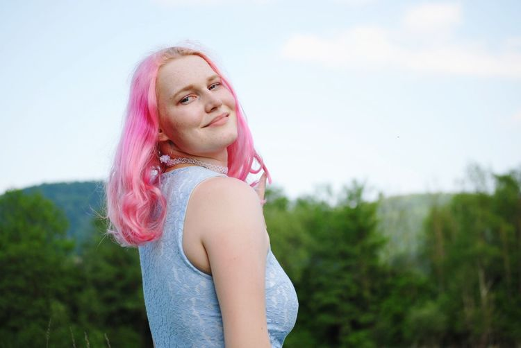 Portrait of smiling young woman with dyed pink hair standing in park