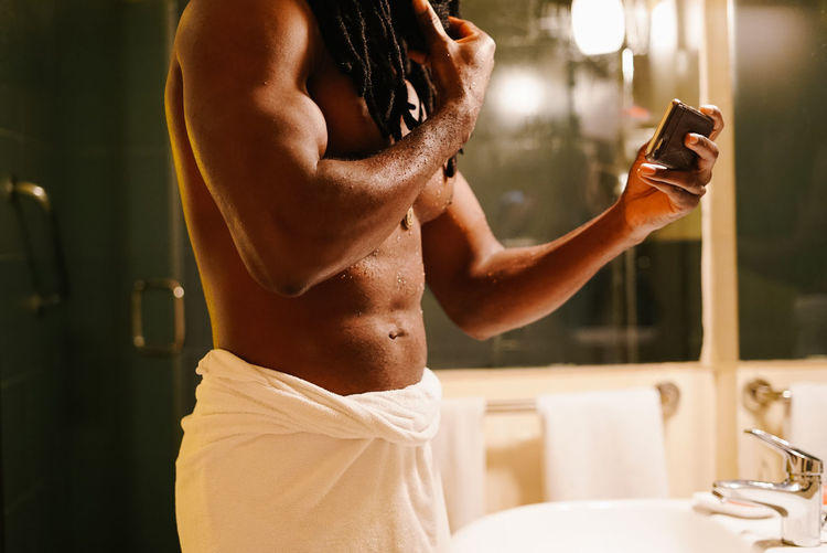 Midsection Of Shirtless Man In Bathroom At Home