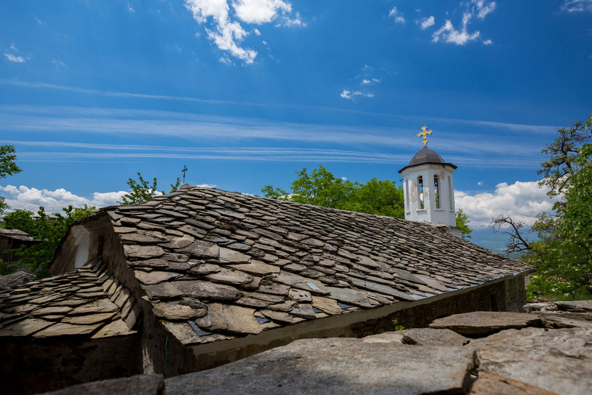 Street view of the tiled stone roof with black cross of very old abandoned orthodox church in Leshten, Bulgaria with its golden cross and the spring blue sky in the background Architecture Bulgaria❤️ Church Kovachevitsa LeshtenBulgaria Retro Rhodopes Travel Travel Photography Traveling Bulgaria Leshten Tiled Roof  Tiles Travel Destinations Vintage