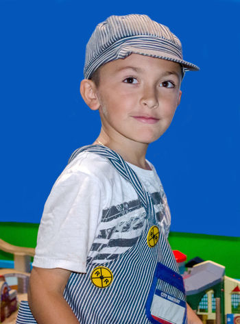 a handsome young boy poses in a train engenier costume. Fun Childhood Child America Clothing Costume Pretending Make Believe Hispanic Boy Male Person