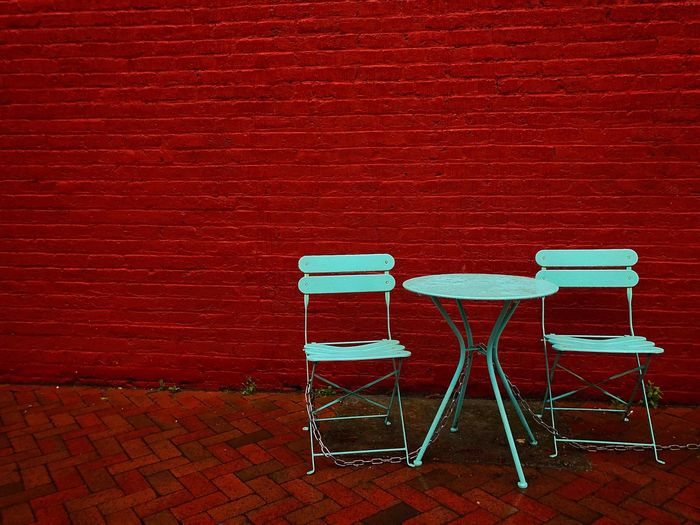 Empty chairs against red wall