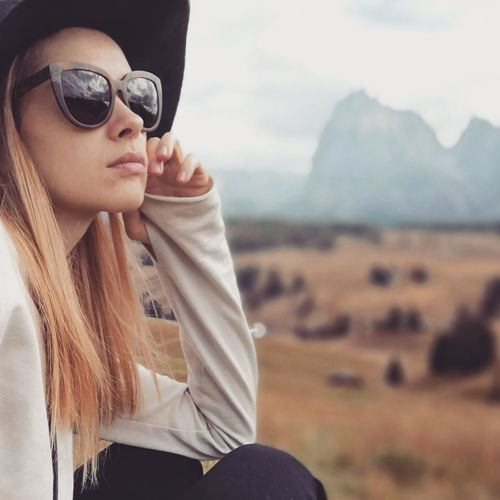 Close-Up Of Woman Wearing Sunglasses Against Mountains