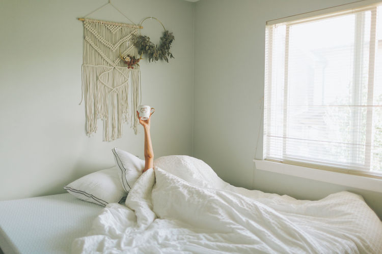 Woman holding coffee mug while wrapped in blanket on bed at home