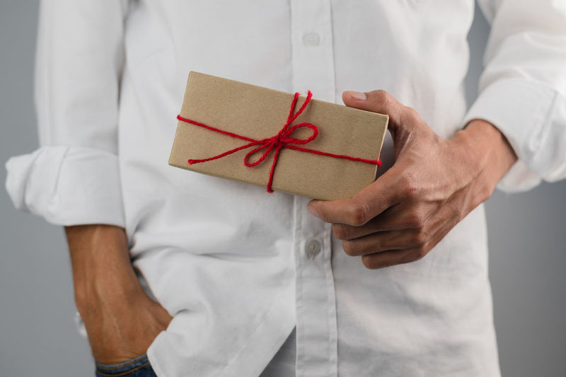 Midsection of man holding paper in box