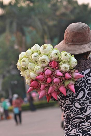 Rear view of woman holding bunch of flowers