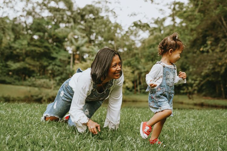 Cheerful mother playing with daughter at park