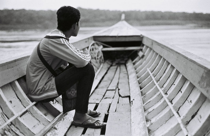 Man Sitting On Boat In Lake