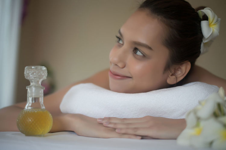 Smiling young woman by oil lying on massage table in spa