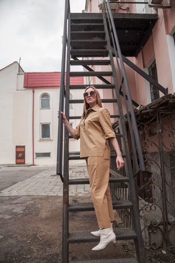 Full length outside portrait of fashion model in sunglasses, beige summer spring suit in urban area