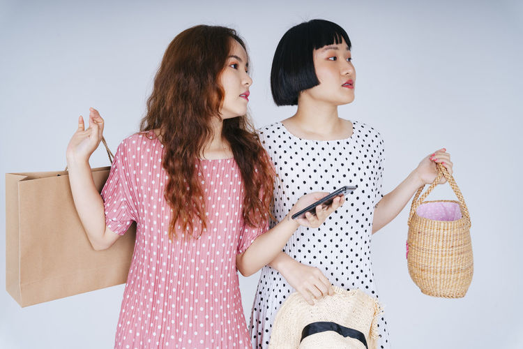 Lesbian couple using smart phone while holding bags against gray background