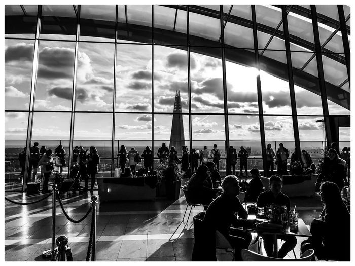 Sunsets on the sky garden IPhone X ShotOnIphone IPhoneography Iphoneonly IPhone Mobile Photography Framed Black And White Bnw Walkie Talkie Sky Garden London Large Group Of People Real People Men Women Lifestyles Indoors  Architecture Sky Sitting Cloud - Sky Leisure Activity Day Crowd People Modern
