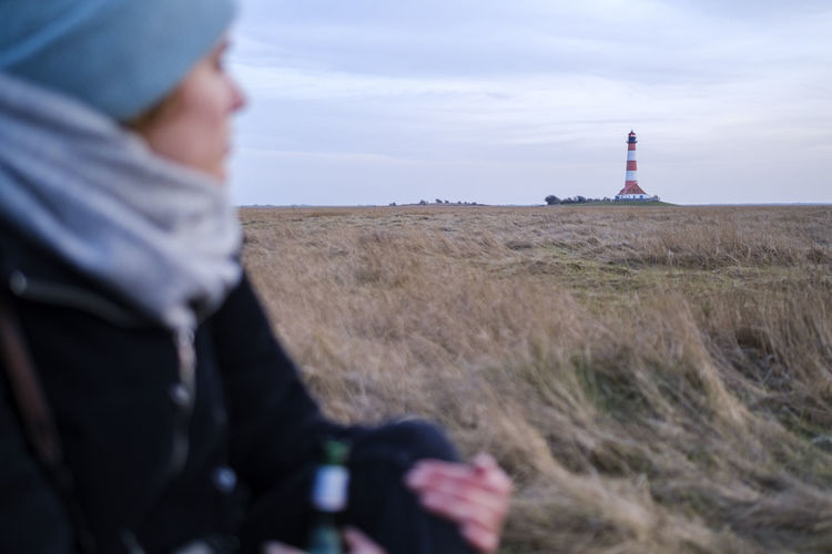 Man on field by lighthouse against sky